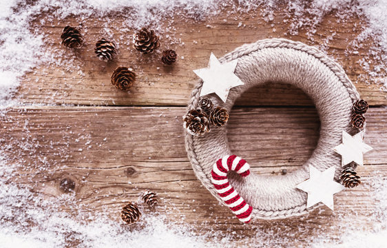 Beautiful woolen Christmas Wreath, decorated with Candy Canes, Pines and Stars on wooden Background