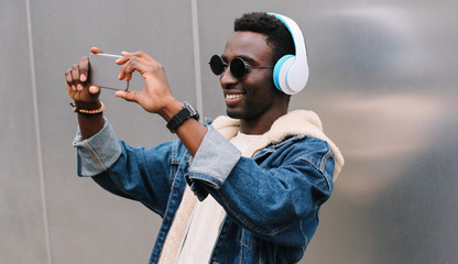 Modern happy smiling young african man taking selfie picture by smartphone while listening to music in wireless headphones on gray wall background