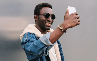 Portrait close up of happy smiling african man taking selfie picture by smartphone on gray wall background