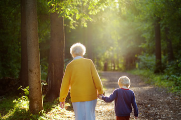 Elderly grandmother and her little grandchild walking together in sunny summer park. Grandma and grandson.