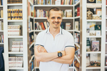Smiling man looking in camera with bookshelfs behind in the library
