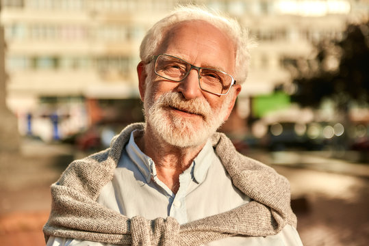Life is beautiful. Portrait of happy and handsome bearded senior man in glasses looking at camera and smiling while spending time outdoors on a sunny day