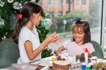 Two little sisters having fun while making christmas Nativity crafts with at home - Real family