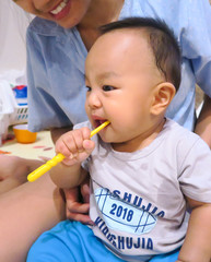 Asian baby boy, 7 months old trying brushing teeth