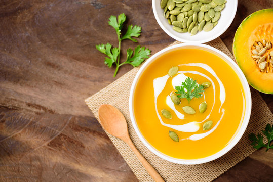 Butternut squash soup with pumpkin seed and cream in bowl, top view