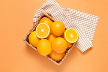 Basket with fresh oranges on color background