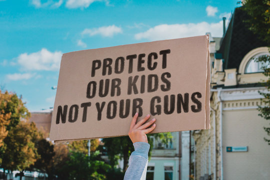 "The phrase "" Protect our kids not your guns "" on a carton banner in men's hand. Human holds a cardboard with an inscription. Gun violence. Law. USA. Ban"