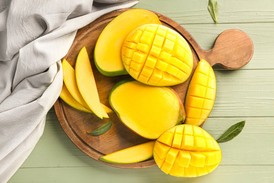 Board with cut mango fruit on table
