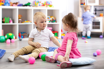 Children playing with colorful toys. Little kid girl and toddler boy in kindergarten. Children play at day care or preschool.