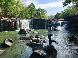 Woman traveler with camera taking a beautiful waterfall photo at Tat Ton national park in Chaiyaphum province, Thailand