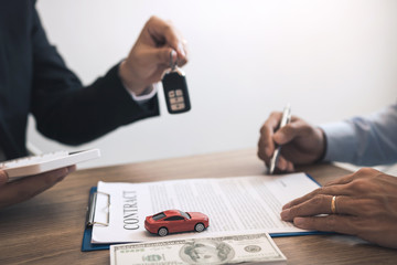 New car buyers sign contract documents for new car purchases at the showroom, the salesperson's office.