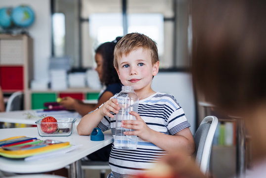 Small school boy sitting at the desk in classroom, drinking water.