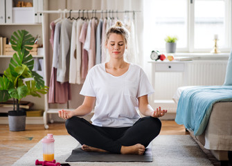 Fotobehang School de yoga Young woman doing yoga exercise indoors at home, meditating.