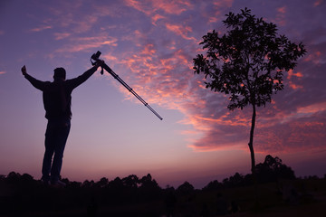 Photographer taking pictures outdoors, silhouette of a man with camera over sunset