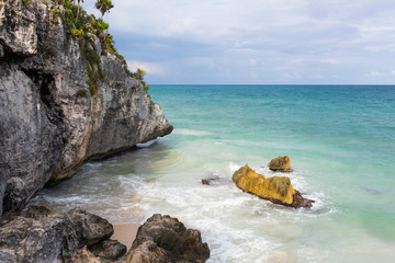 Cliff face and boulders on beach in Tulum, Mexico.