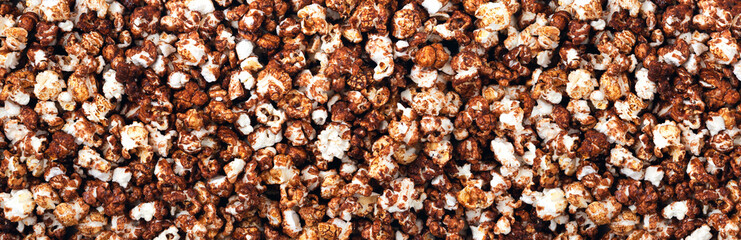 Background and texture of chocolate popcorn. Panorama. View from above. Banner.