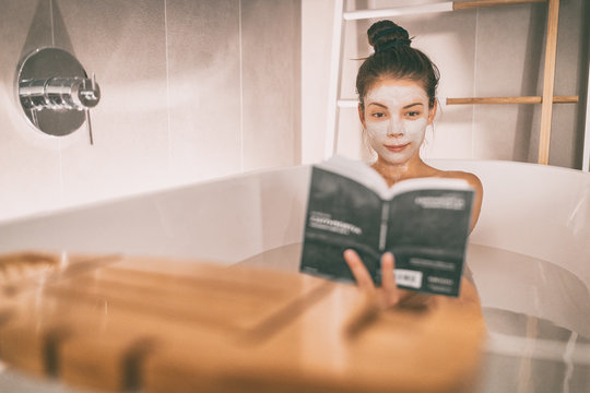 Woman reading book in warm bathtub taking a bath relaxing at home - pamper wellness Asian girl pampering skin care with facial mask treatment.