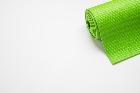 Green Yoga mat for Yoga, Pilates exercise at home or gym rolled on white background with copy space for your text