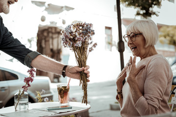 Delighted aged woman looking at the flowers