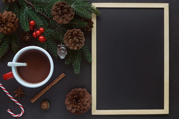 Foto auf Acrylglas Schokolade Black granite table decorate with blackboard or chalkboard, pine leaf and cones and cup of chocolate in Christmas concept. Background in top view flat lay with copy space for Christmas wallpaper.