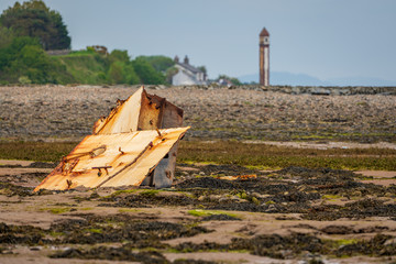 A rusty part of a  shipwreck in the mud of the Walney Channel with the Rampside Lighthouse in the background, seen from the road to Roa Island, Cumbria, England, UK