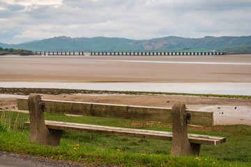 A bench overlooking the low tide at Morecambe Bay with Leven Viaduct in the background, seen from Canal Foot, Cumbria, England, UK