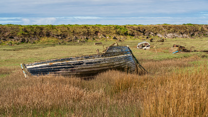 The wrecks of four boats in the grass, seen in Askam-in-Furness, Cumbria, England, UK