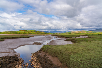 A small branch of the River Esk with clouds over Lake District in the background, seen near Newbiggin, Cumbria, England, UK