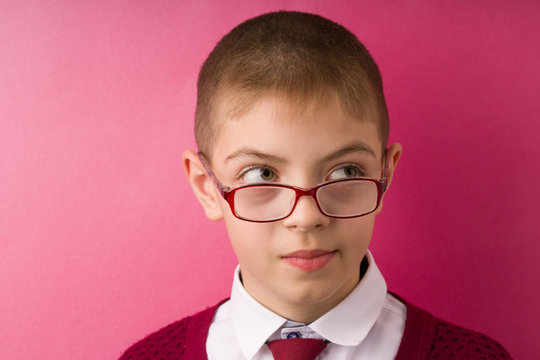 Closeup portrait kid with glasses avoiding eye contact looking side got in unpleasant awkward situation feels embarrassed. red background