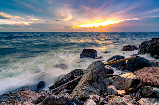 Ocean water splash on rock beach with beautiful sunset sky and clouds. Sea wave splashing on stone at sea shore on summer. Nature landscape. Tropical paradise beach at sunset. Rock beach at coast.