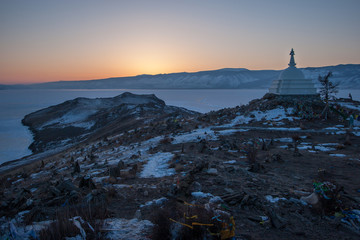 Foto op Canvas Brazilië Sunset on Ogoy island on Lake Baikal overlooking a Buddhist stupa, a frozen lake and mountains behind it. The sun is just around the corner, the sky is orange.
