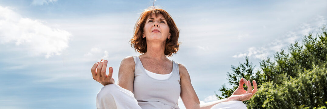 beautiful middle aged woman sitting in yoga lotus position, banner