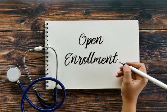 Top view of stethoscope and hand writing Open Enrollment on notebook on wooden background.