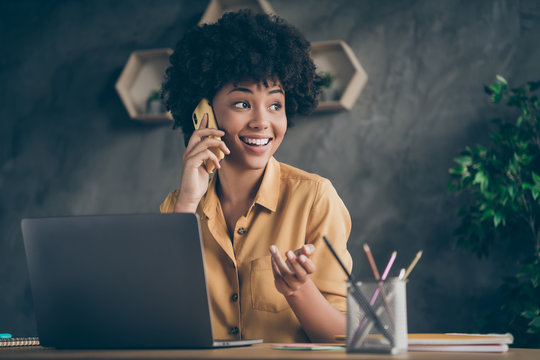 Photo of cheerful positive mixed-race pretty woman working as content manager arranging with her customers by phone smiling toothily