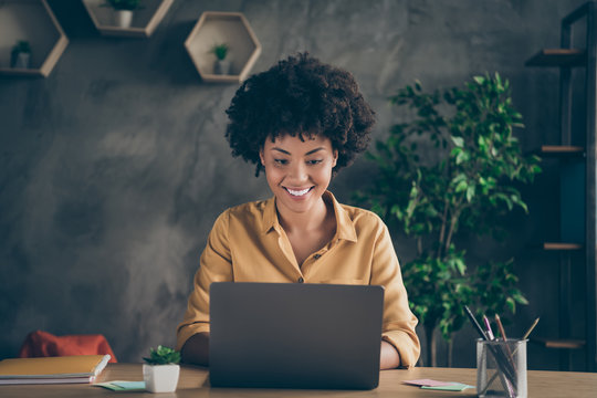 Photo of cheerful business woman working on reports of her boss expecting to be praised for done work at table desktop