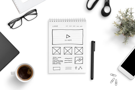 Sketch of a website on a paper writing pad, surrounded by smart phone, cup of coffee, glasess, plant. Office desk, top view, flat lay.