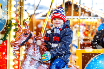 Adorable little kid boy riding on a merry go round carousel horse at Christmas funfair or market, outdoors. Happy child having fun on traditional family xmas market in Cologne, Germany