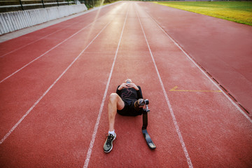Fotomurales - Handsome caucasian handicapped young sporty man dressed in sportswear and with artificial leg lying on racetrack and listening music over smart phone.
