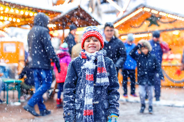 Little cute kid boy having fun on traditional German Christmas market during strong snowfall.. Happy child enjoying traditional family market in Germany, Dresden. Laughing boy in colorful clothes