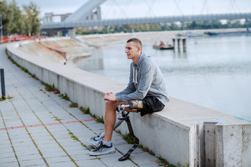 Fotomurales - Handsome sporty caucasian handicapped man in sportswear and with artificial leg sitting on quay.