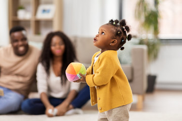 childhood and people concept - little african american baby girl playing with ball and parents at home