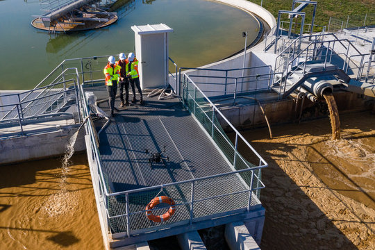 Engineers assesing waste treatment plant with drone