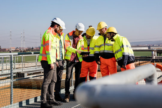 Engineers and workers assesing wastewater plant