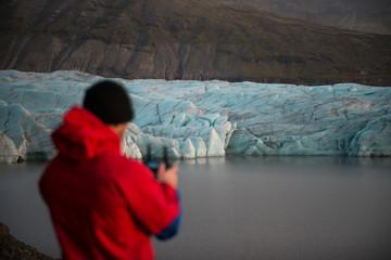 chico pilotando dron en frente de un glaciar