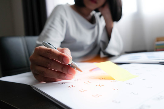 Asian woman is writing something on yellow paper note or calendar to remind the meeting, data preparation, take appointment protect for mistake or get information for shopping online. work at home