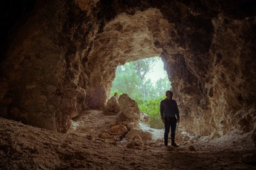 Young man inside a cave posing with jeans and a jacket