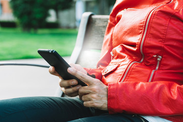 woman hands with red jacket using a smartphone