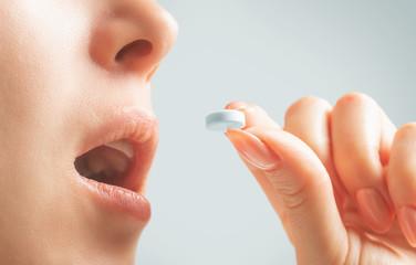 Unrecognizable woman taking a white round pill.