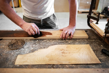 Carpenter applying stain to a briar root panel