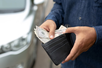 Businessman Person holding a wallet in the hands of take money out of pocket stand front car prepare pay by installments - insurance, loan and buying car finance concept insurance, payment a car - fototapety na wymiar